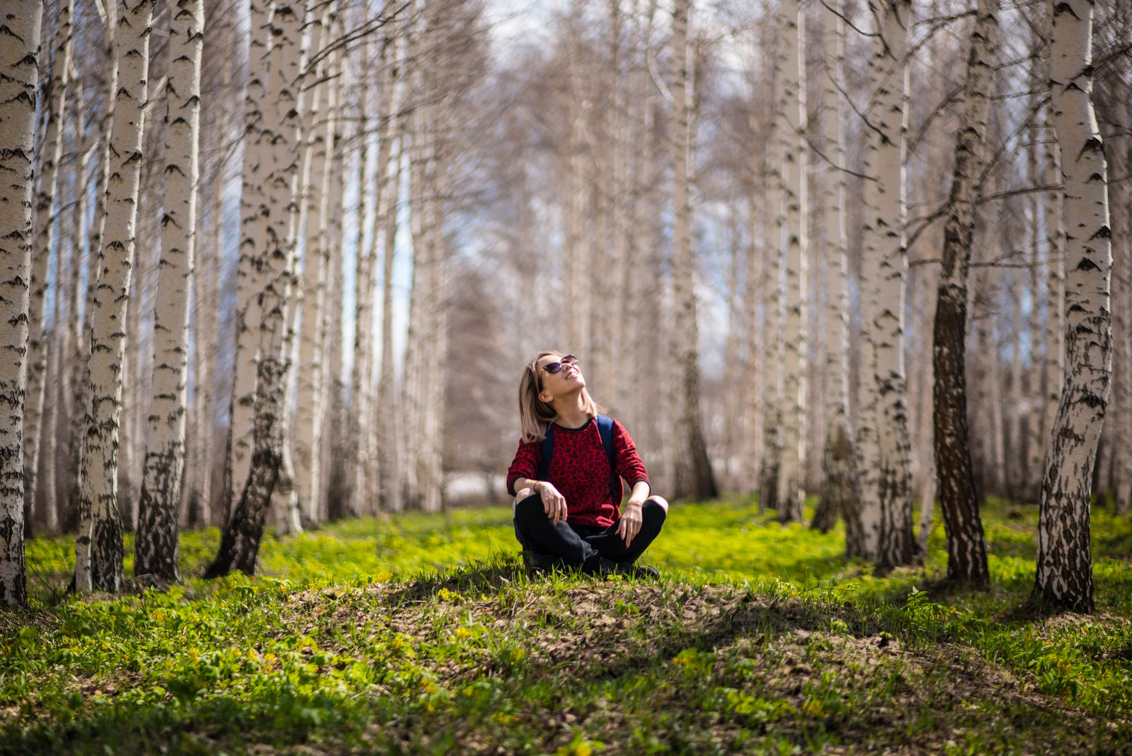 Woman sat on the floor smiling and looking up at the trees around her