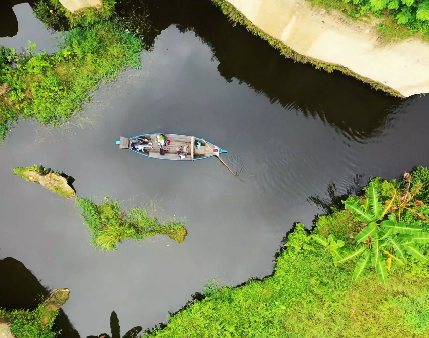 Birdseye view of a small boat gently being rowed along a river
