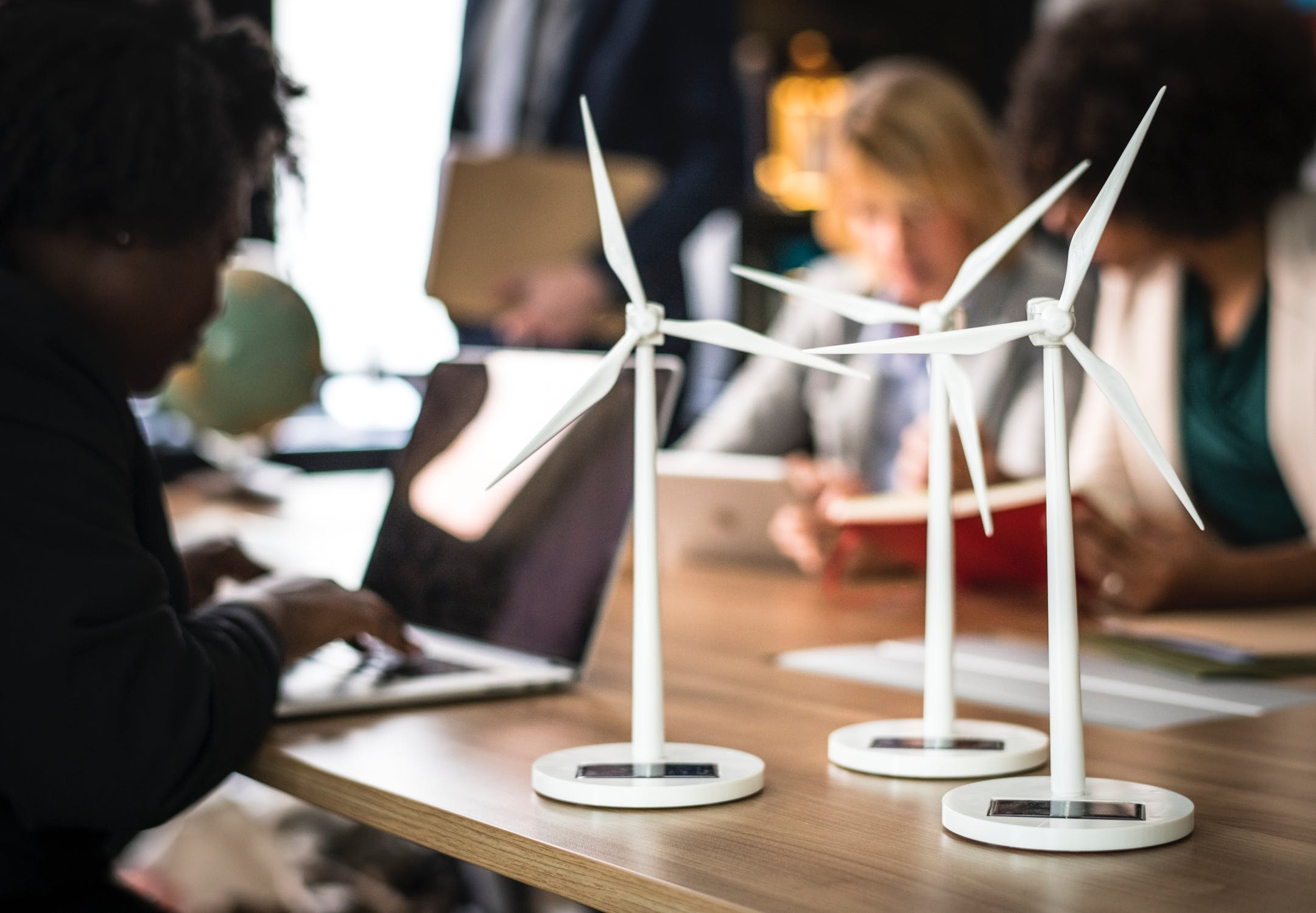 Small renewable wind farm models on a table with people working behind