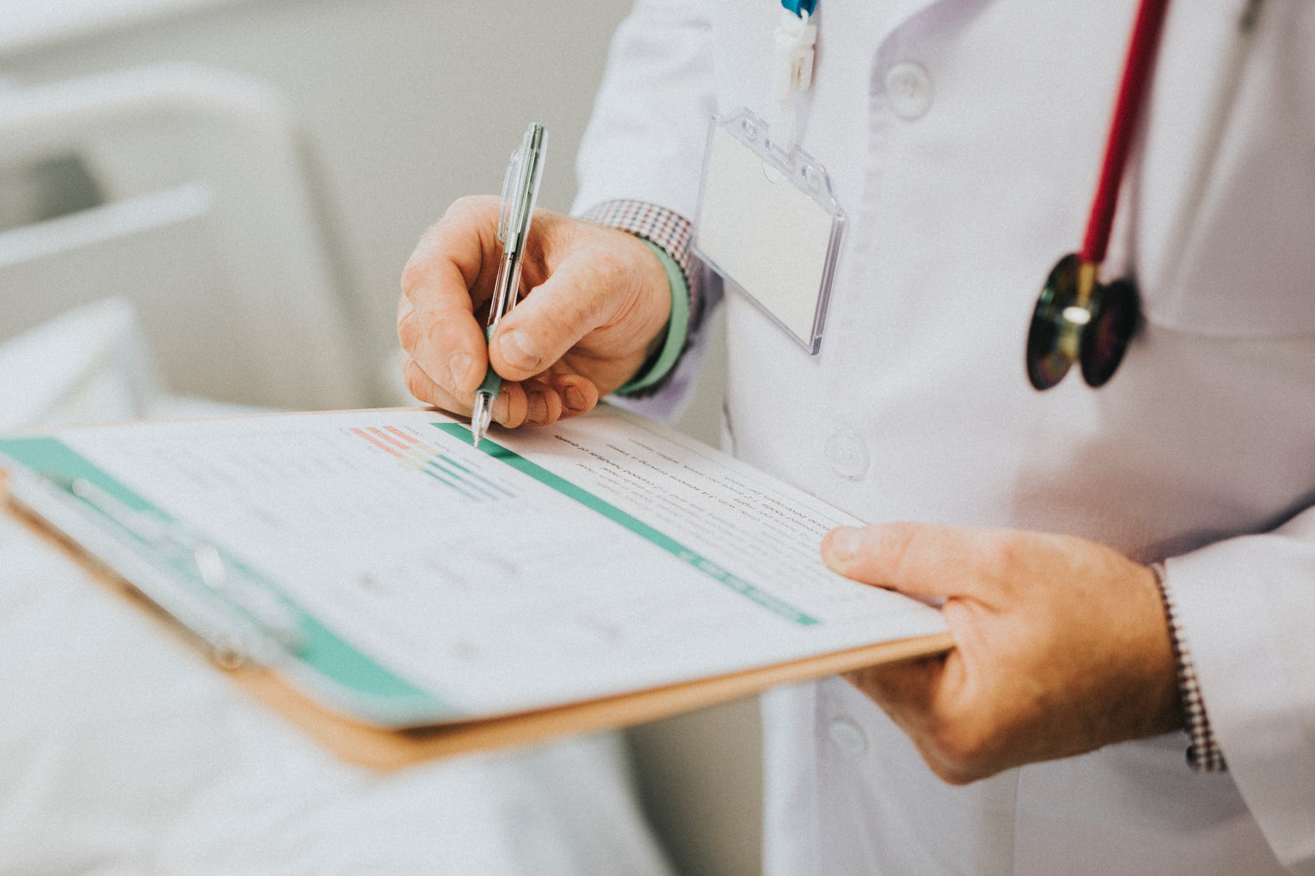 Doctor in a white lab coat standing and filling out a medical form